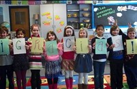 Children standing in a line holding up letters that spell 'Gracias'